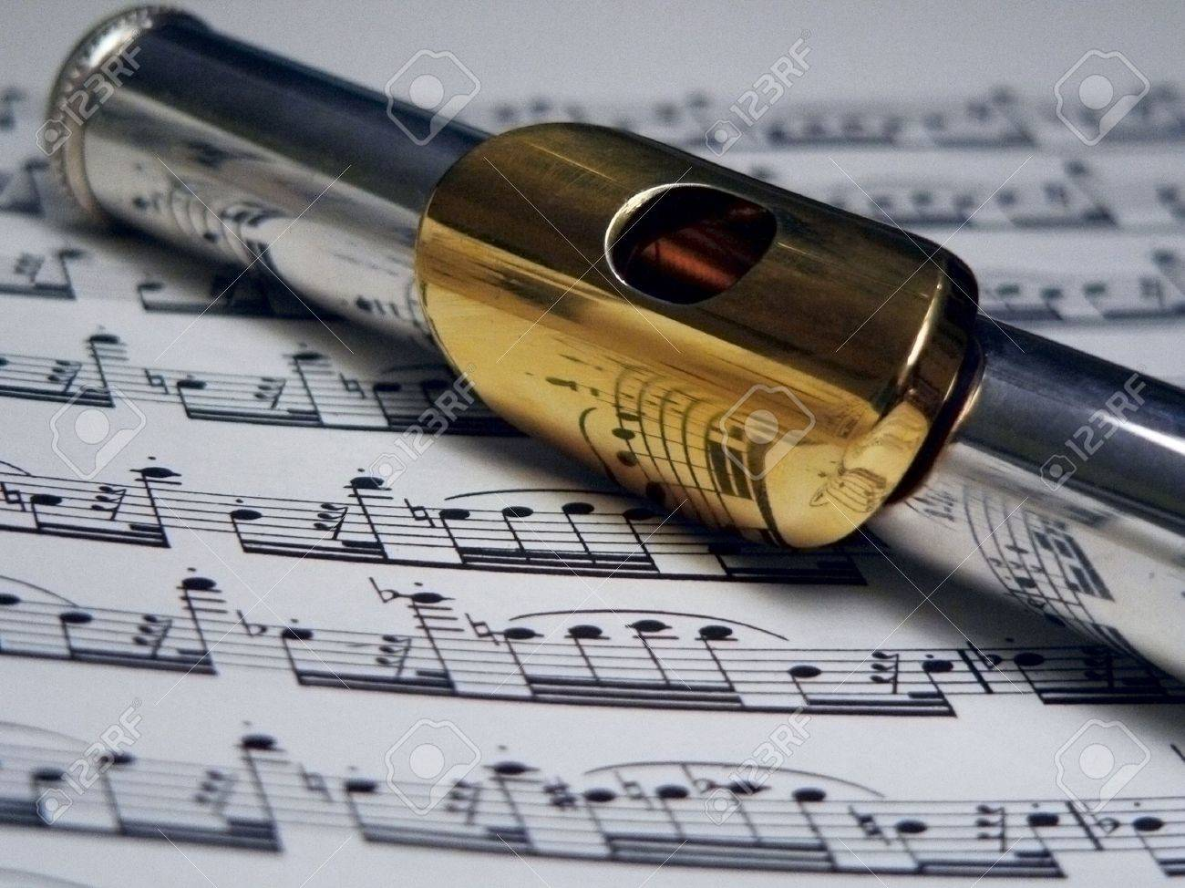 flute with gold mouthpiece on sheet music Stock Photo - 204696