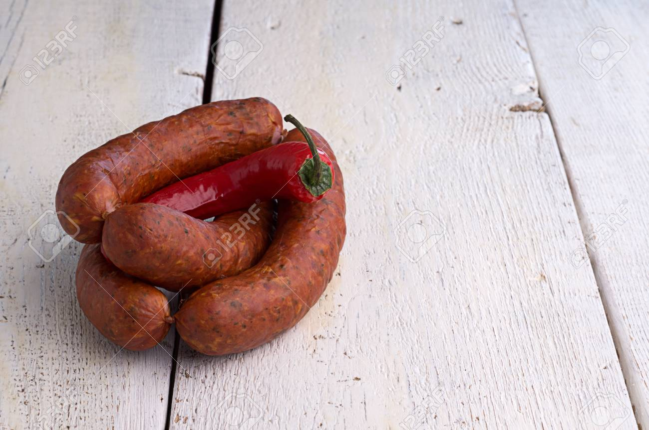 smoked sausage, peppercorns, red hot chili pepper on old wooden table Stock Photo - 18661170