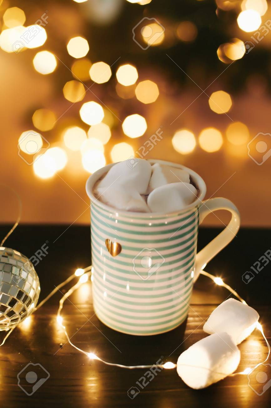 christmas coffee cup with marshmallows on the background of new years lights and decorations stock photo