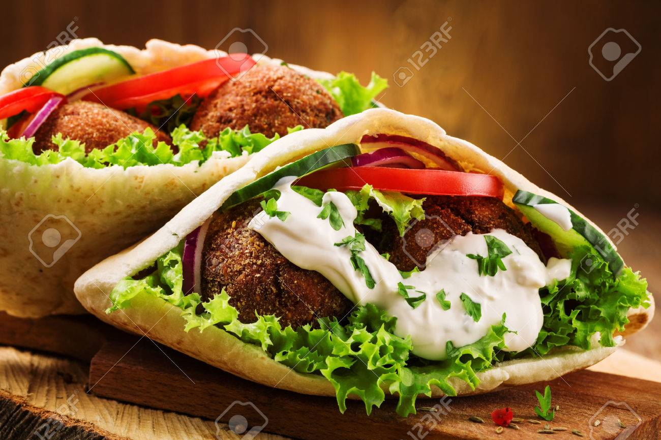Falafel and fresh vegetables in pita bread on wooden table - 46295574