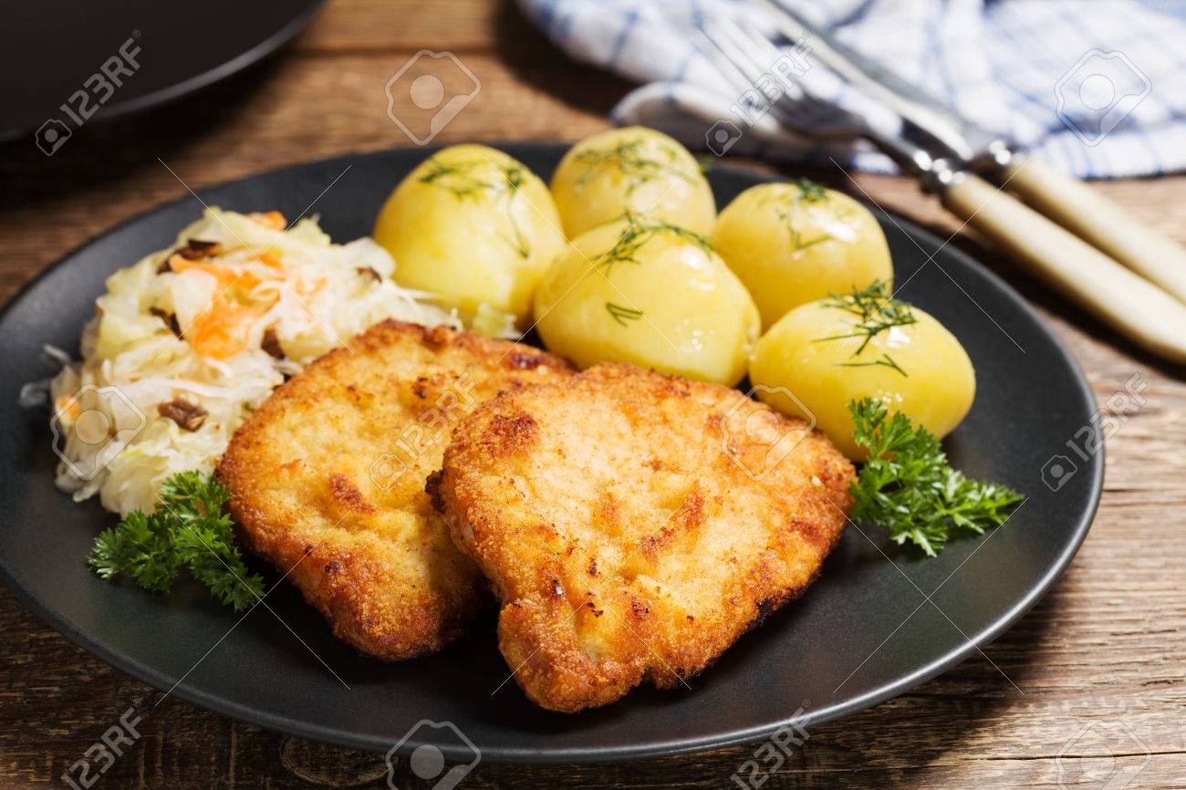 Fried Pork Chop In Breadcrumbs Served With Boiled Potatoes And Cabbage Traditional Polish Dish