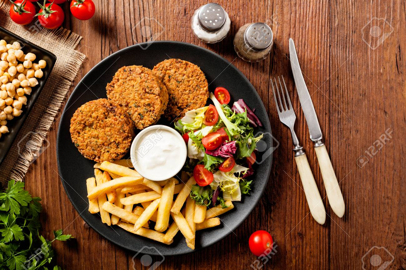 Serving Of Falafel And Chips Served On A Black Plate With Sauce Stock Photo Picture And Royalty Free Image Image 96044341