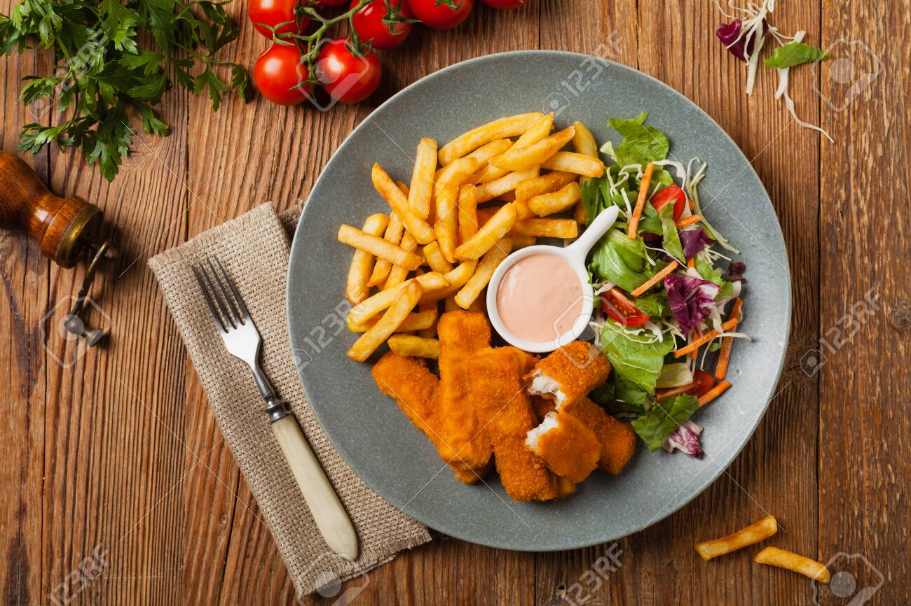 Fish sticks with fries and salad on grey plate. Top view. - 126564577