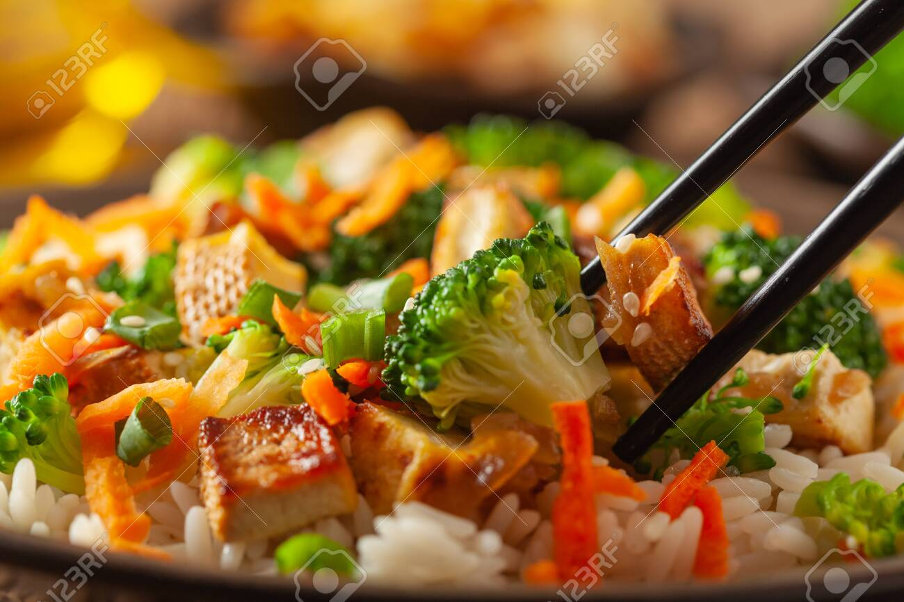 Tofu with rice and vegetables. Served on brown plate. Close up. - 142227580
