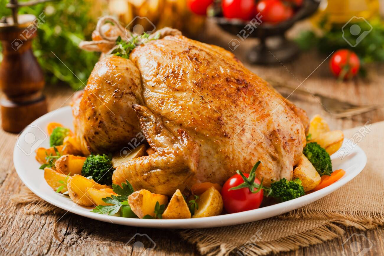 Roast chicken whole. Served on a plate with vegetables and baked potatoes. Front view. - 148179847