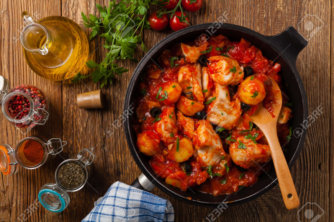 Traditionally prepared cod in Spanish. Served in tomato sauce with boiled potatoes, olivki and basil. Top view. - 155722257
