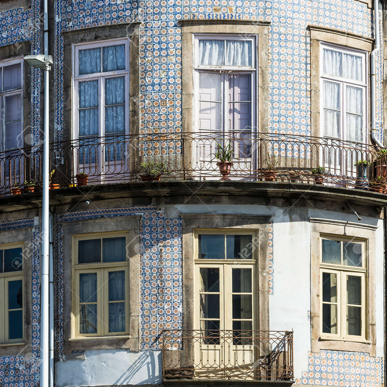 Traditional Portuguese ceramic tiles of azulejo decorate a facade of the old house in the city of Porto - 150368489