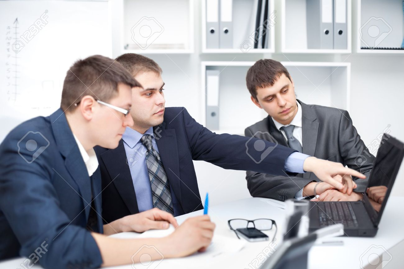 team of young business men working at laptop together in a office stock photo team of young business men working at laptop together in a office