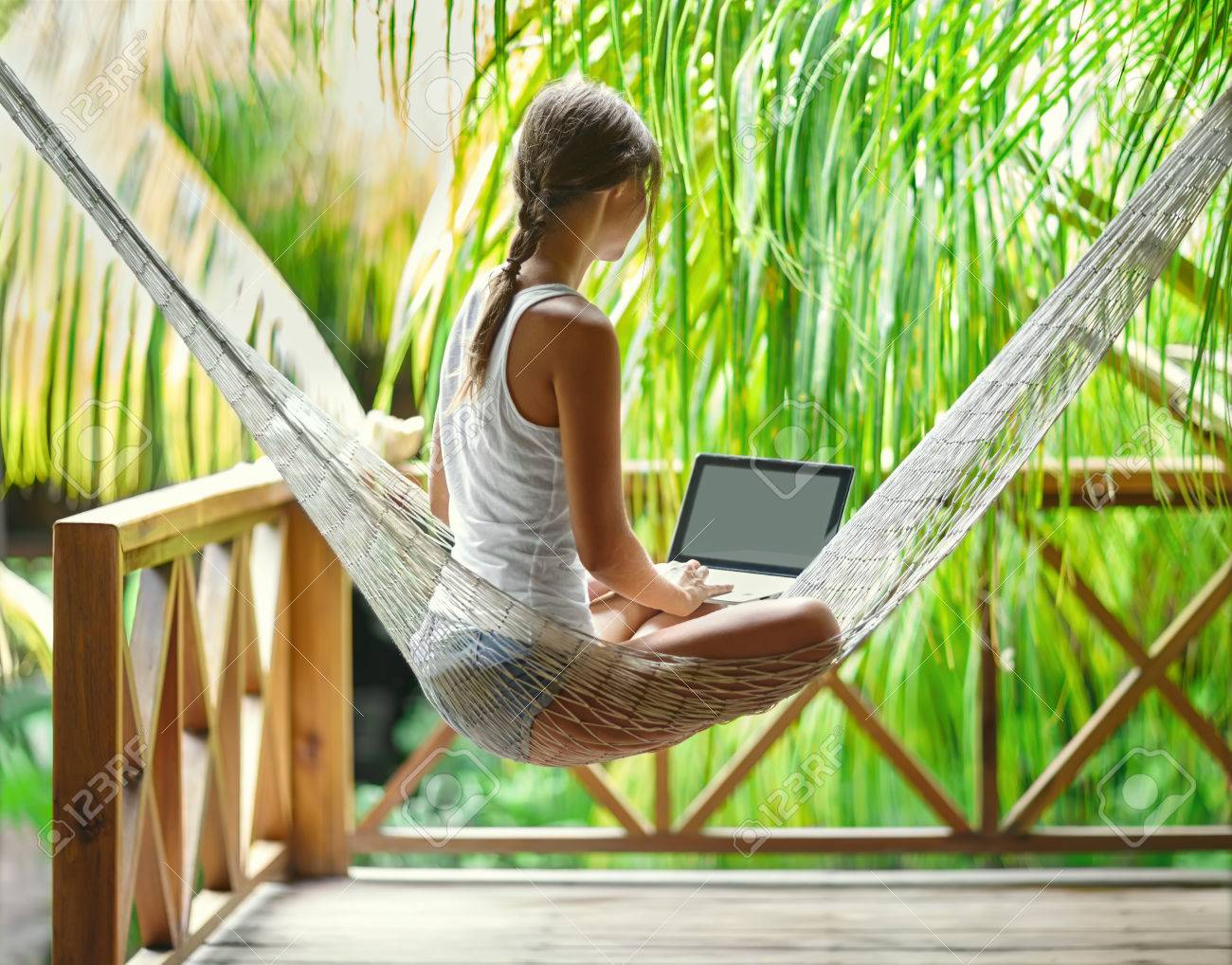 Young beautiful woman sitting in a hammock with laptop in a tropical resort. back view. - 54675126