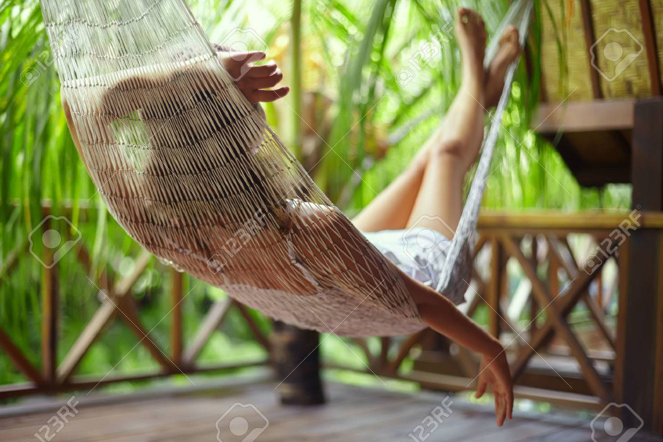 Young beautiful woman relaxing in hammock in a tropical resort.back view - 54675226