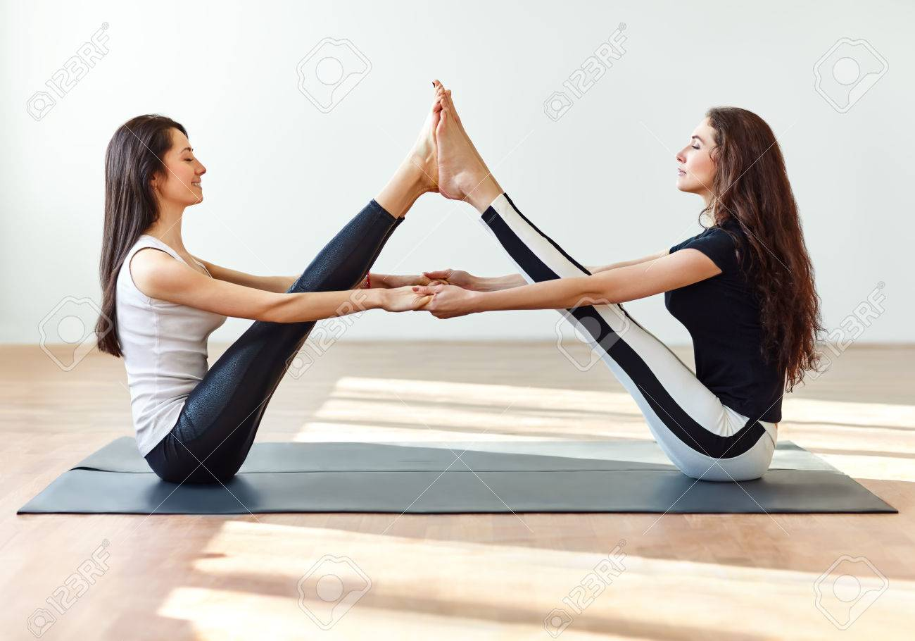 Two Young Women Doing Yoga Asana Buddy Boat Pose Paripurna Navasana Stock Photo Picture And Royalty Free Image Image 60825145