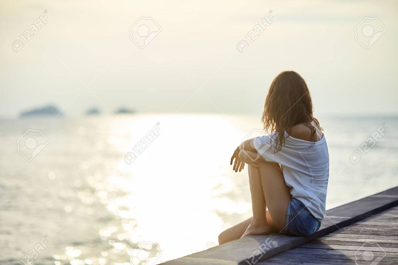 Young beautiful woman sitting on the pier enjoying sunset with copy space - 61521833
