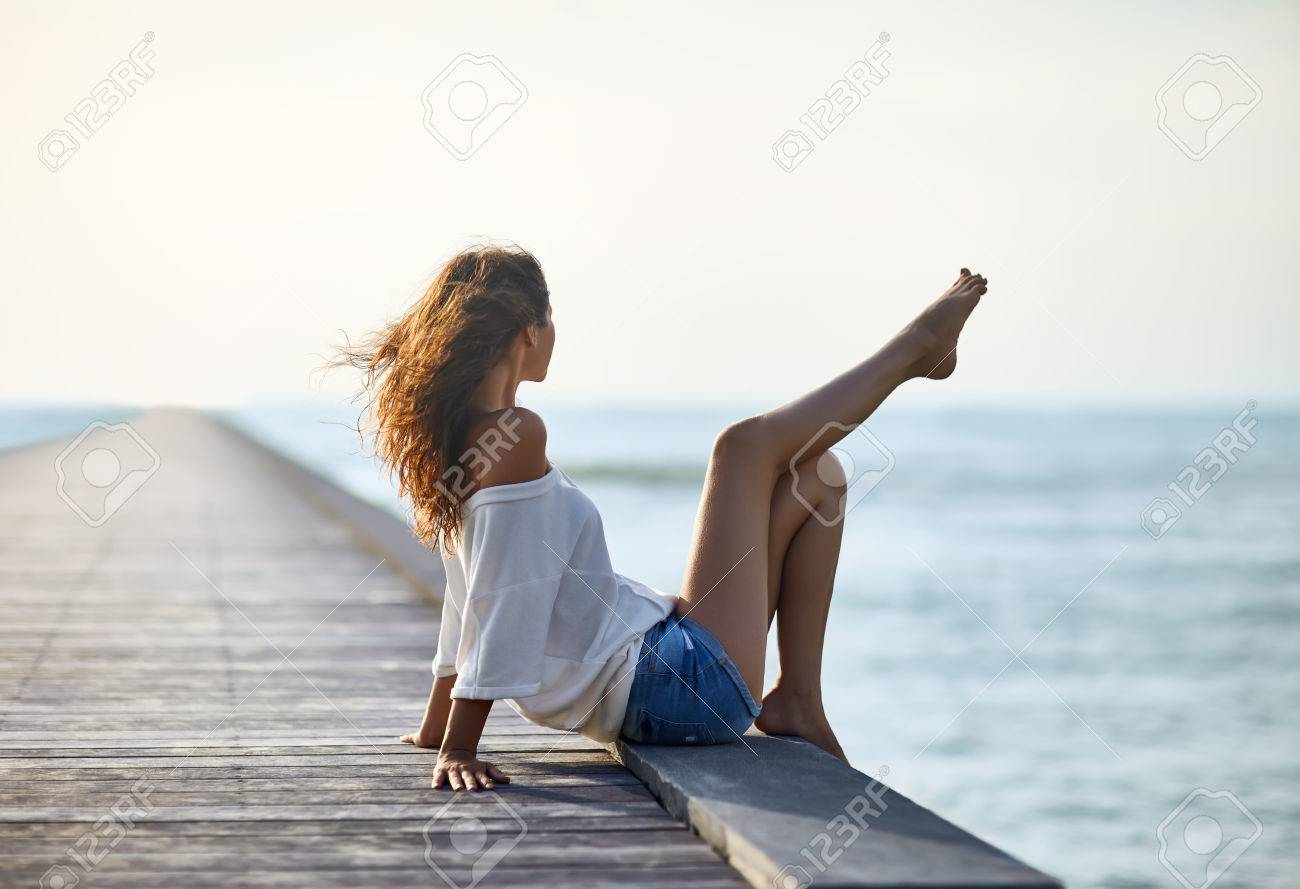 Sexy beautiful woman relaxing on pier with sea view. Vacation concept - 61521863