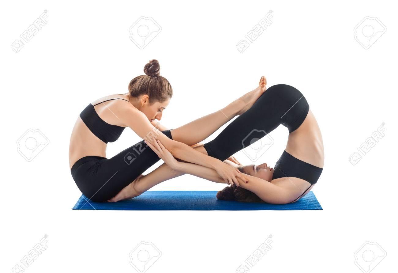 Foto de archivo - Yoga pareja aislada sobre fondo blanco. Dos mujeres  jóvenes haciendo yoga asana. 7d9a93a3a9fc