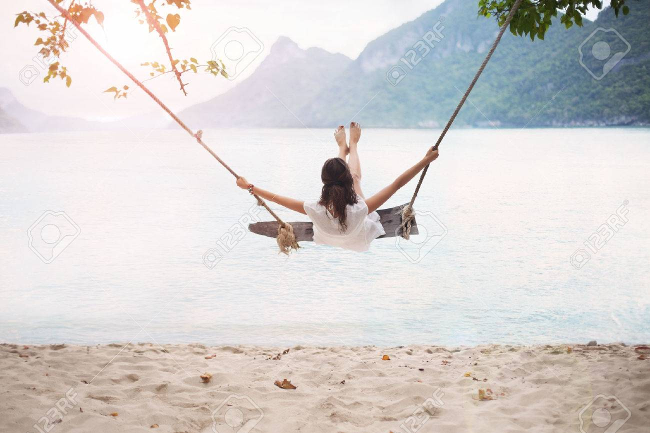 Carefree happy woman on swing on beautiful paradises beach in Thailand Stock Photo - 75254090