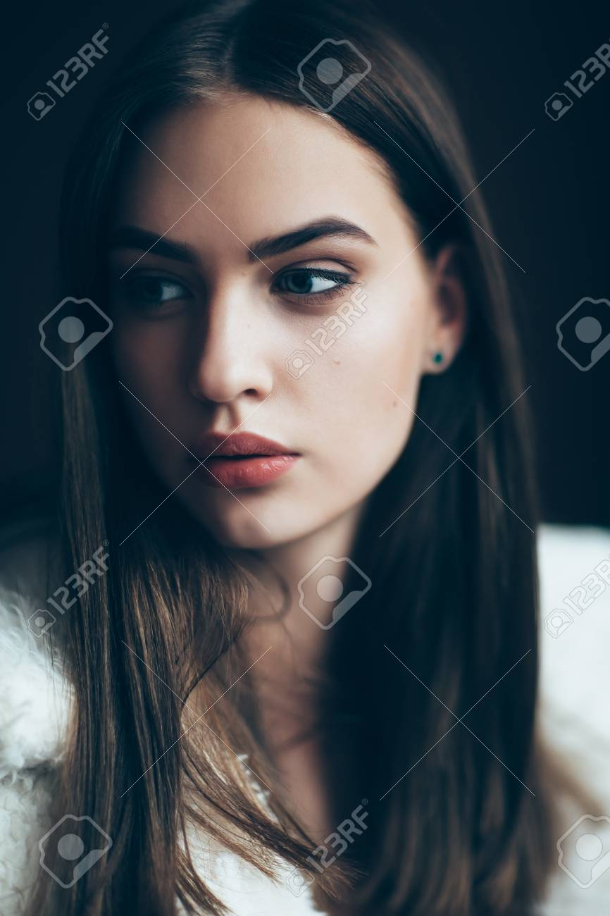 Young beautiful woman portrait, close-up. Pretty girl with red lipstick and stylish hairdo. Pensive look of the female model - 94379354