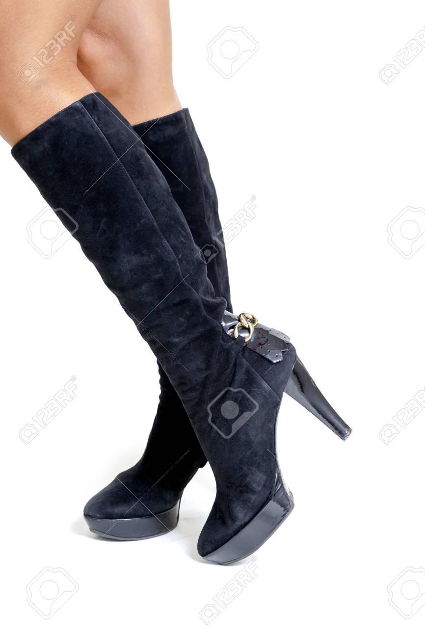 Jambes féminines galbées en bottes en daim noir à la mode avec des talons. Vue de côté sur un fond blanc