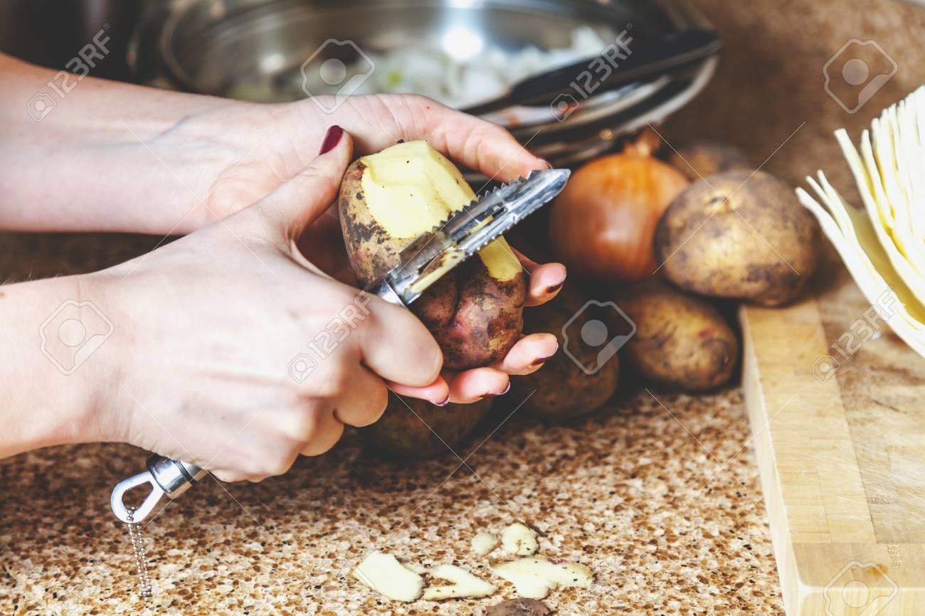 Küchenarbeit. Die Hände Des Kochs Schälen Kartoffeln Mit Einem ...