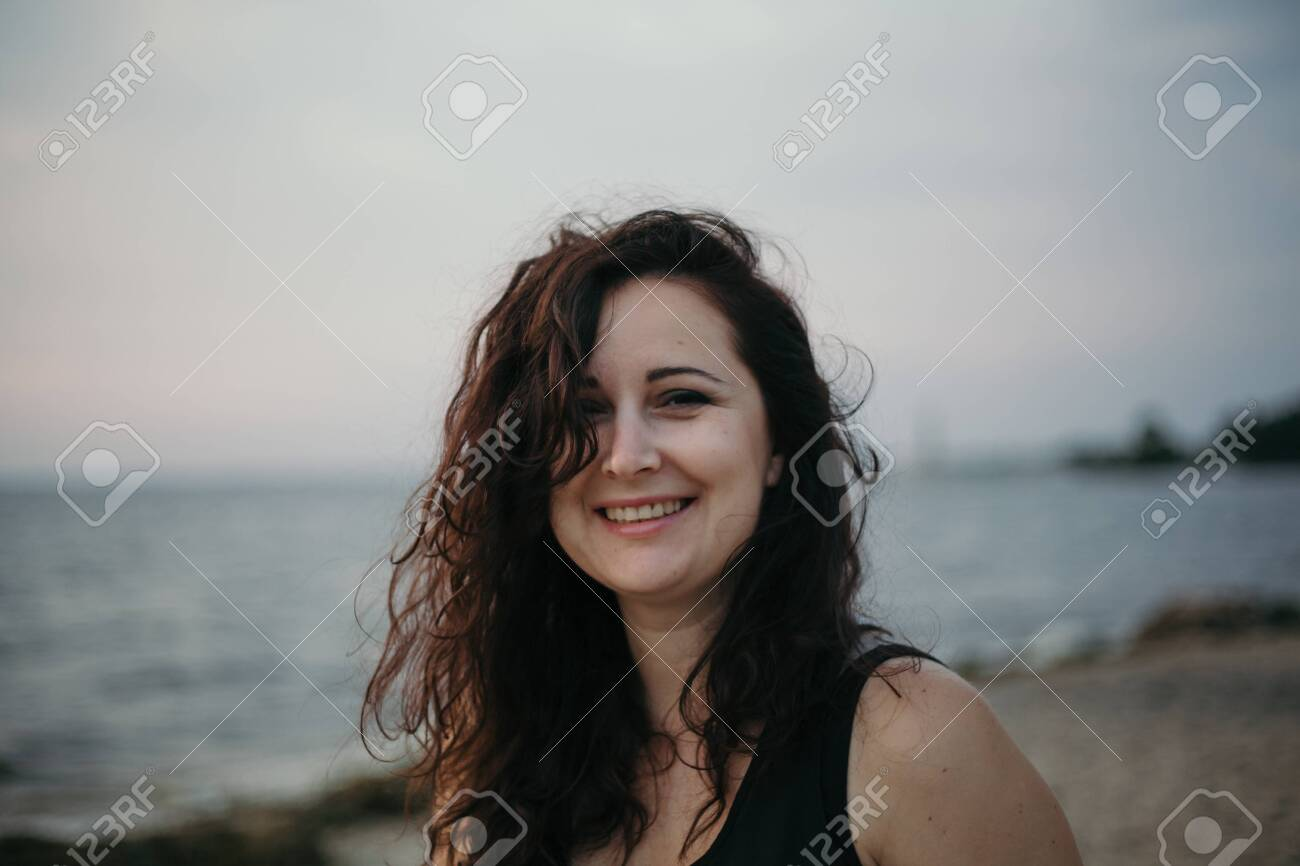 Portrait of a pretty girl with long red hair on the background of a blurred seashore. - 126032049
