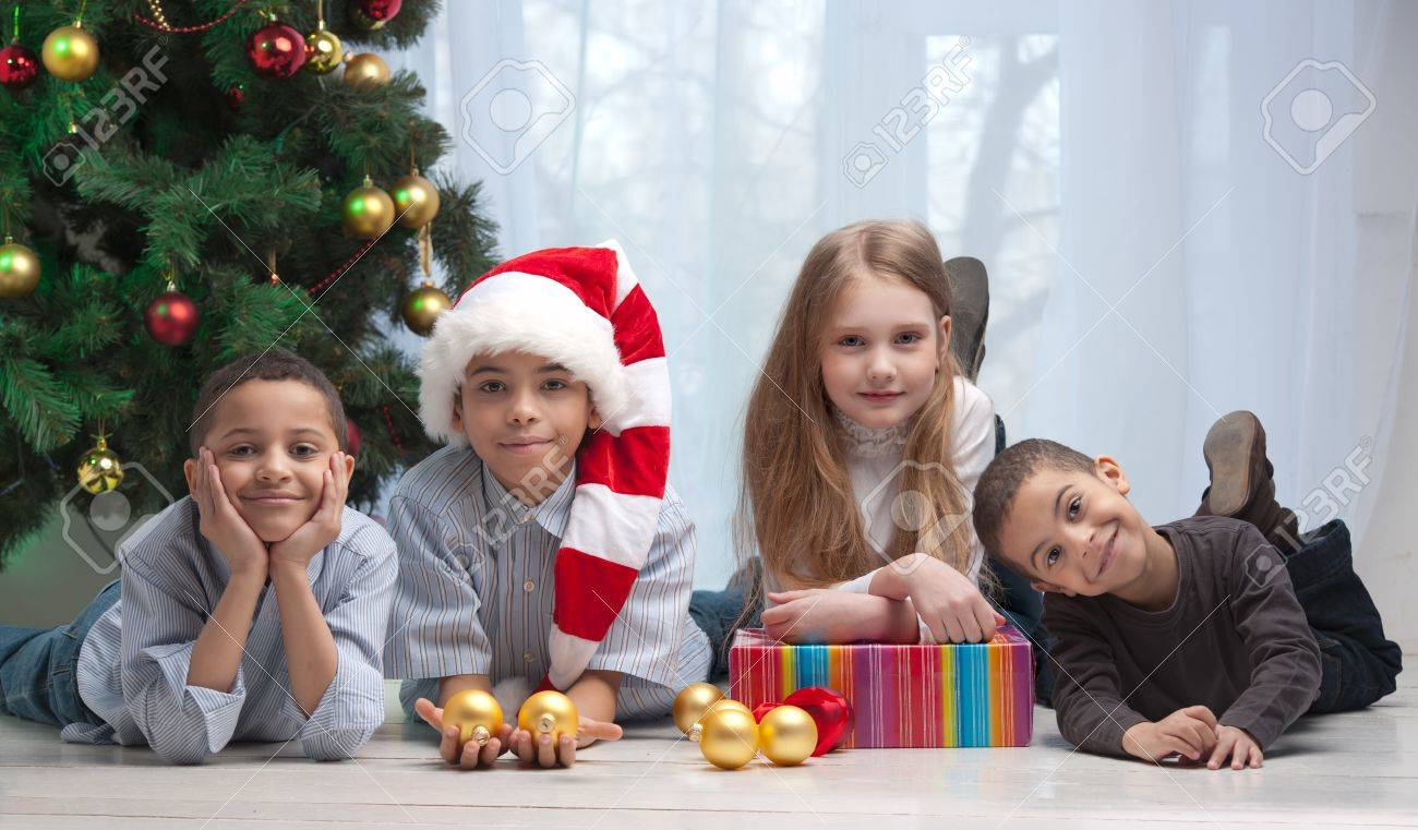 Happy children holding Christmas gifts and sitting on the floor Stock Photo - 13758663
