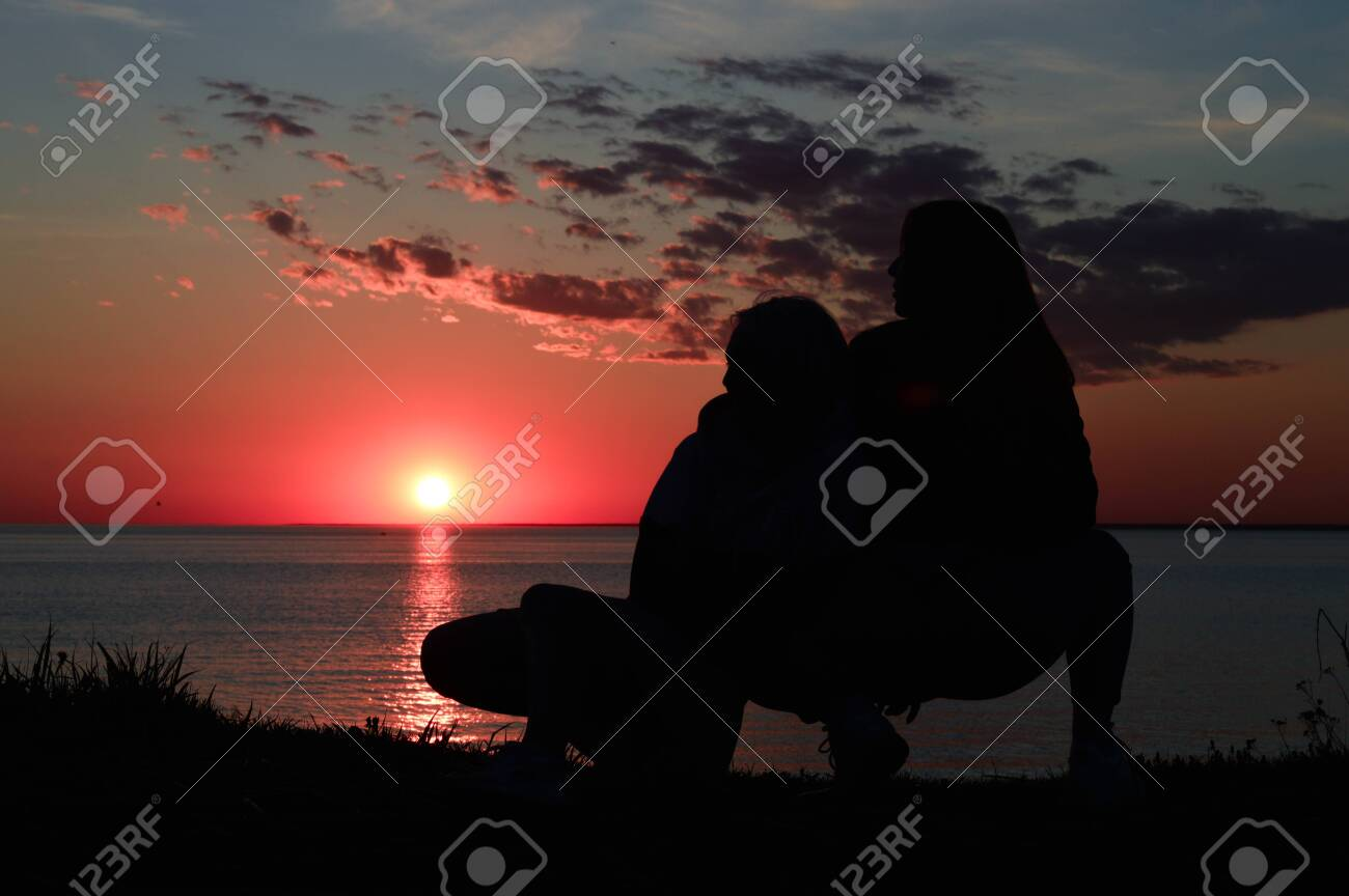 silhouettes of two girls on the shore by the sea. two girls are sitting next to - 148009973