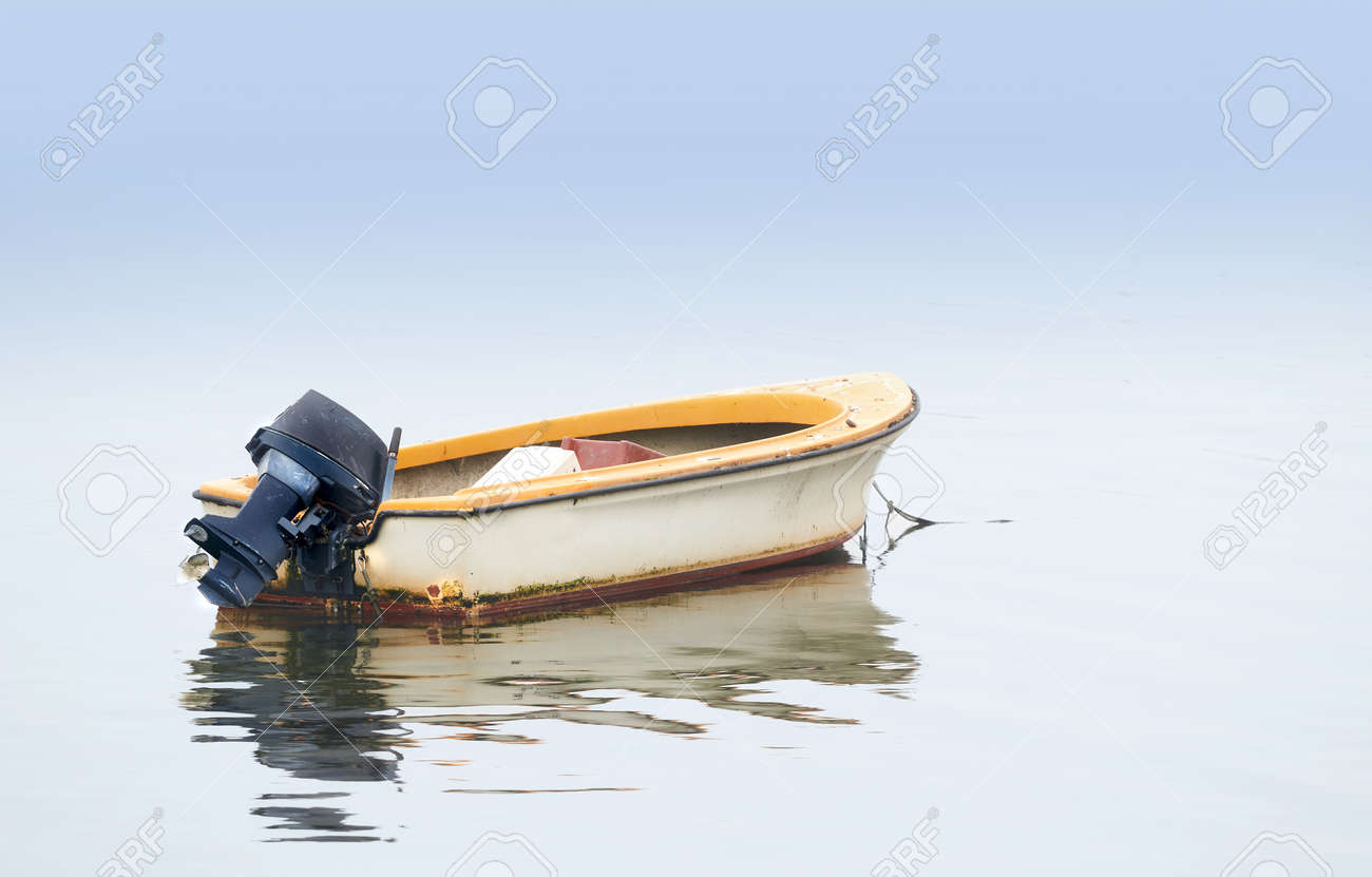 a photo of small boat an early foggy morning stock photo picture