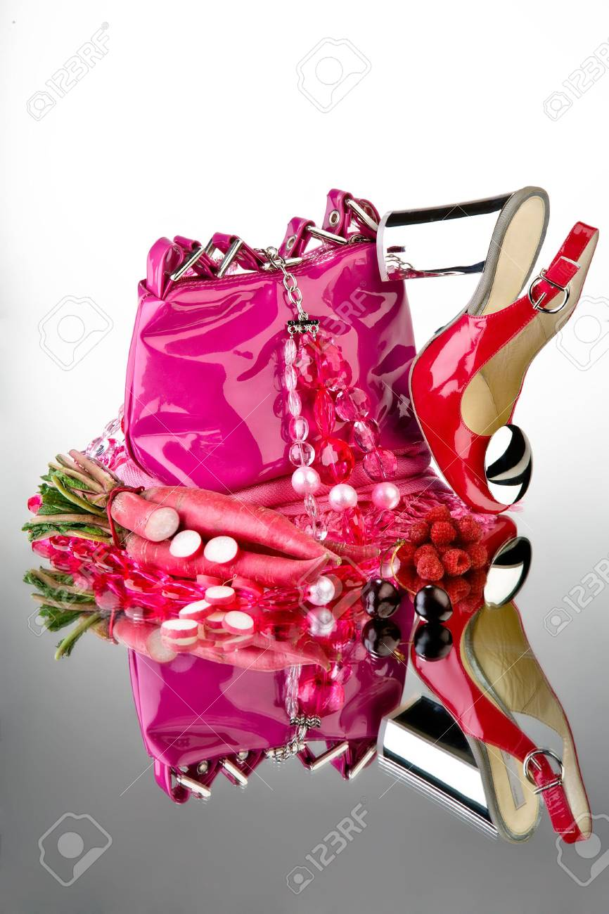 Pink shoes and purse. Pink shoes and purse with accessories and vegetable on a reflective mirror table. Stock Photo - 4081348