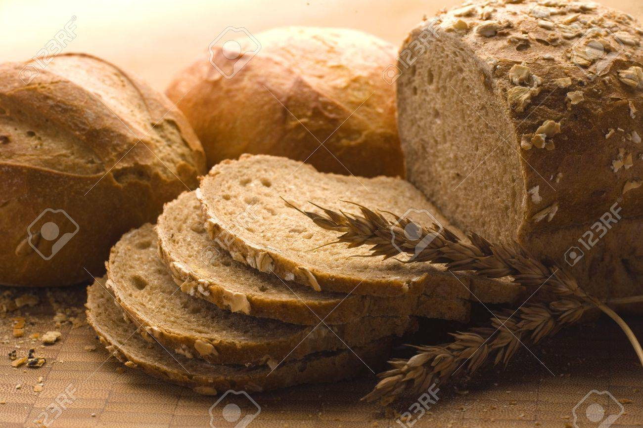 Fresh bread with ear of wheat. Still life view of freshly baked bread with part broken off, and ear of wheat. Stock Photo - 4169770