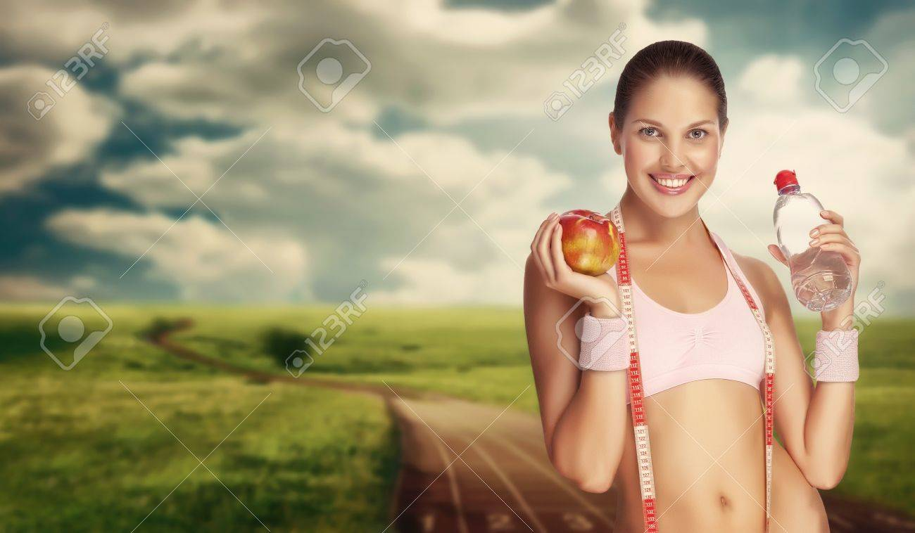A young athletic woman holding water and apple against running track. Stock Photo - 9239657