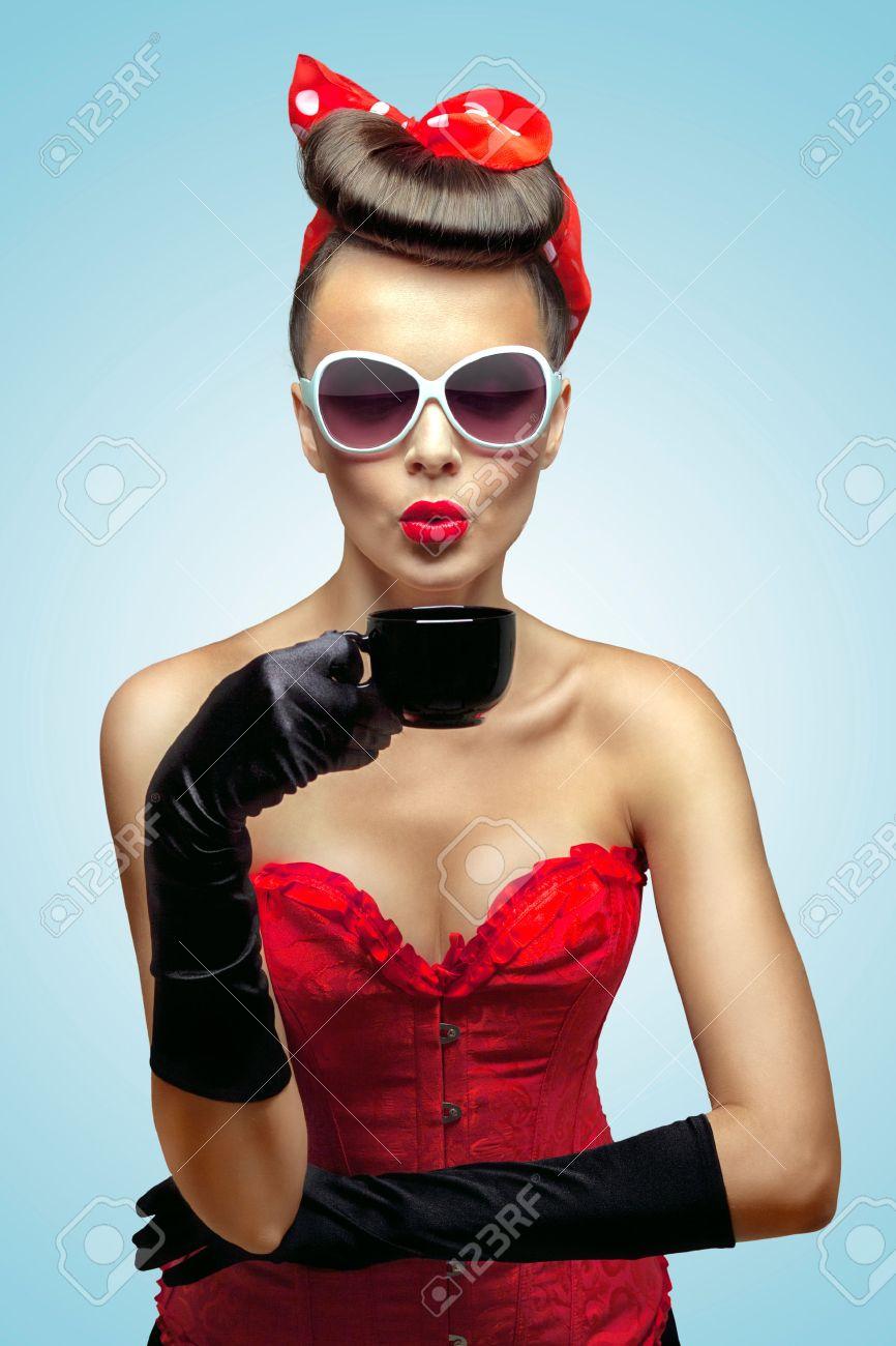 Der Vintage Foto von Glamour Pin up girl vintage Handschuhen und Kühlen  einer heißen Tasse Kaffee