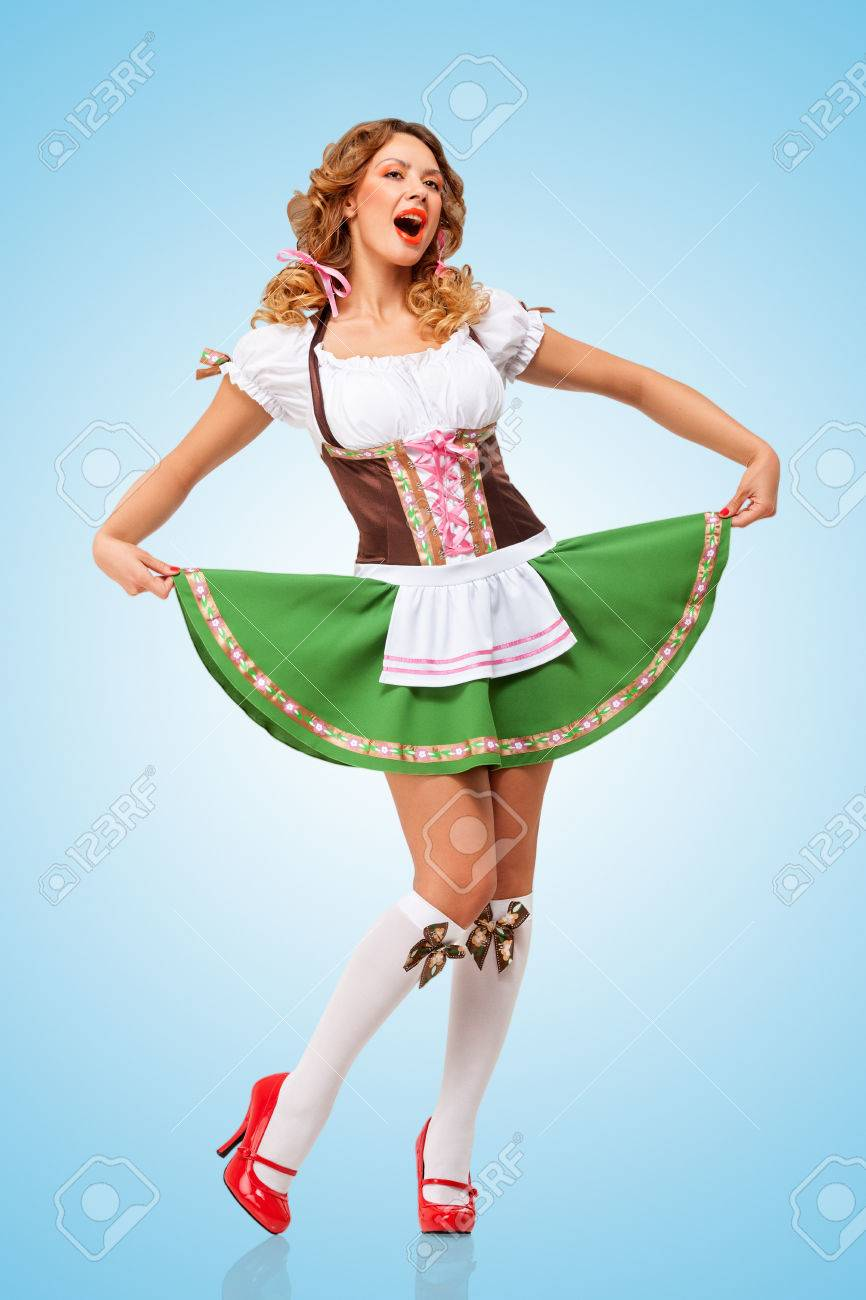 98b5d35d3b13 Stock Photo - Young sexy Oktoberfest woman wearing a traditional Bavarian  dress dirndl dancing and singing on blue background.