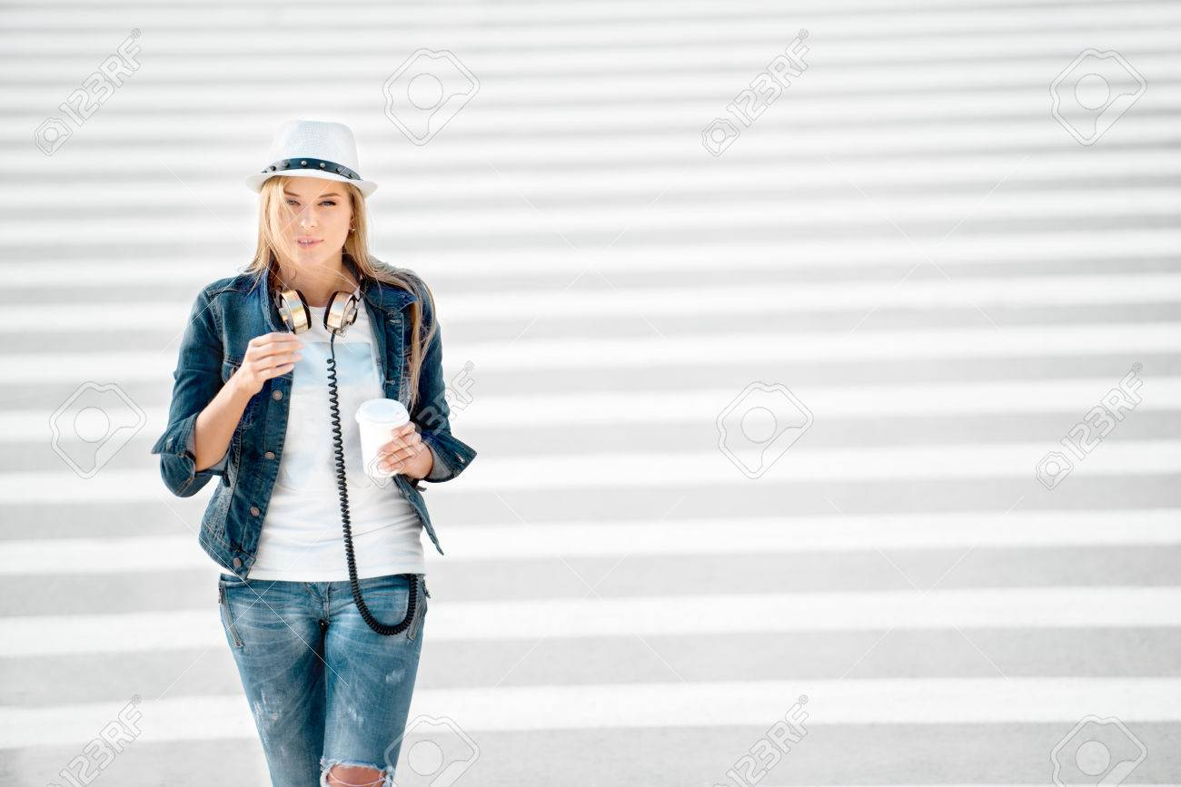 huge discount 45266 72d6c Bella giovane donna in una giacca cappello e jeans con una tazza di caffè  da asporto, in piedi sulla strada con strisce pedonali, bere il caffè, e ...