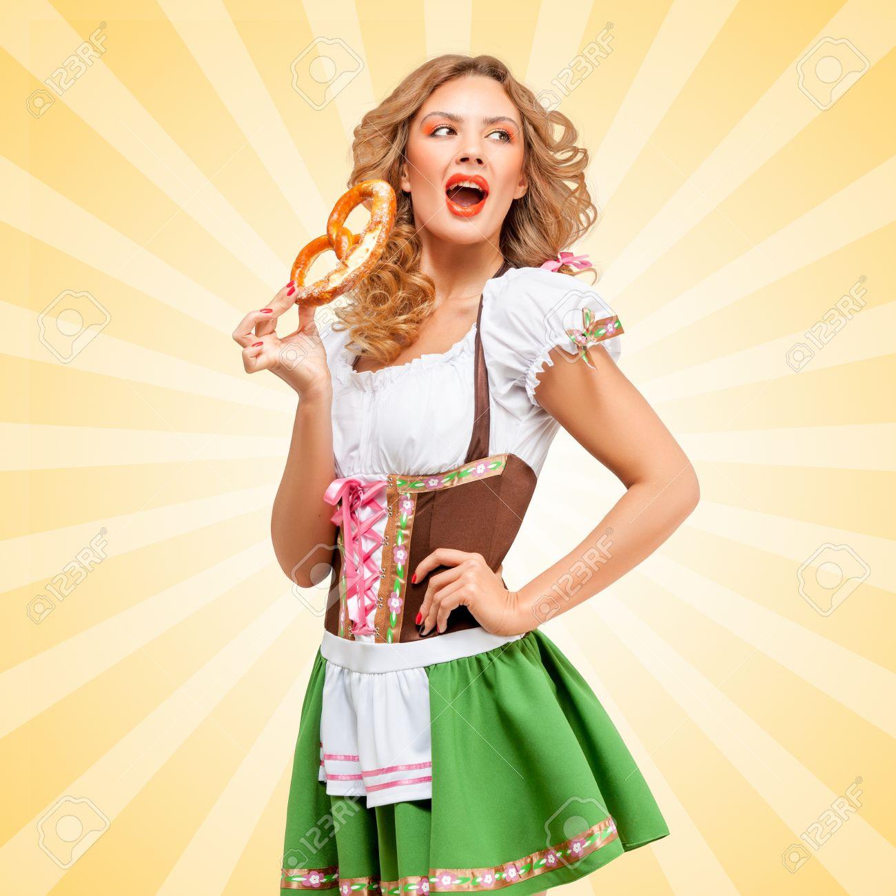 la moitié 5586a a9519 Belle femme Oktoberfest sexy vêtue d'une robe bavaroise traditionnelle  dirndl avec la bouche ouverte mangeant un bretzel sur coloré abstrait de  style ...