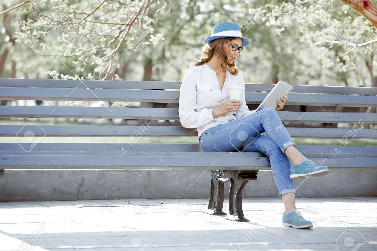 Happy young student with a tablet and a disposable coffee cup sitting on the bench and reading in a summer park. - 51083093