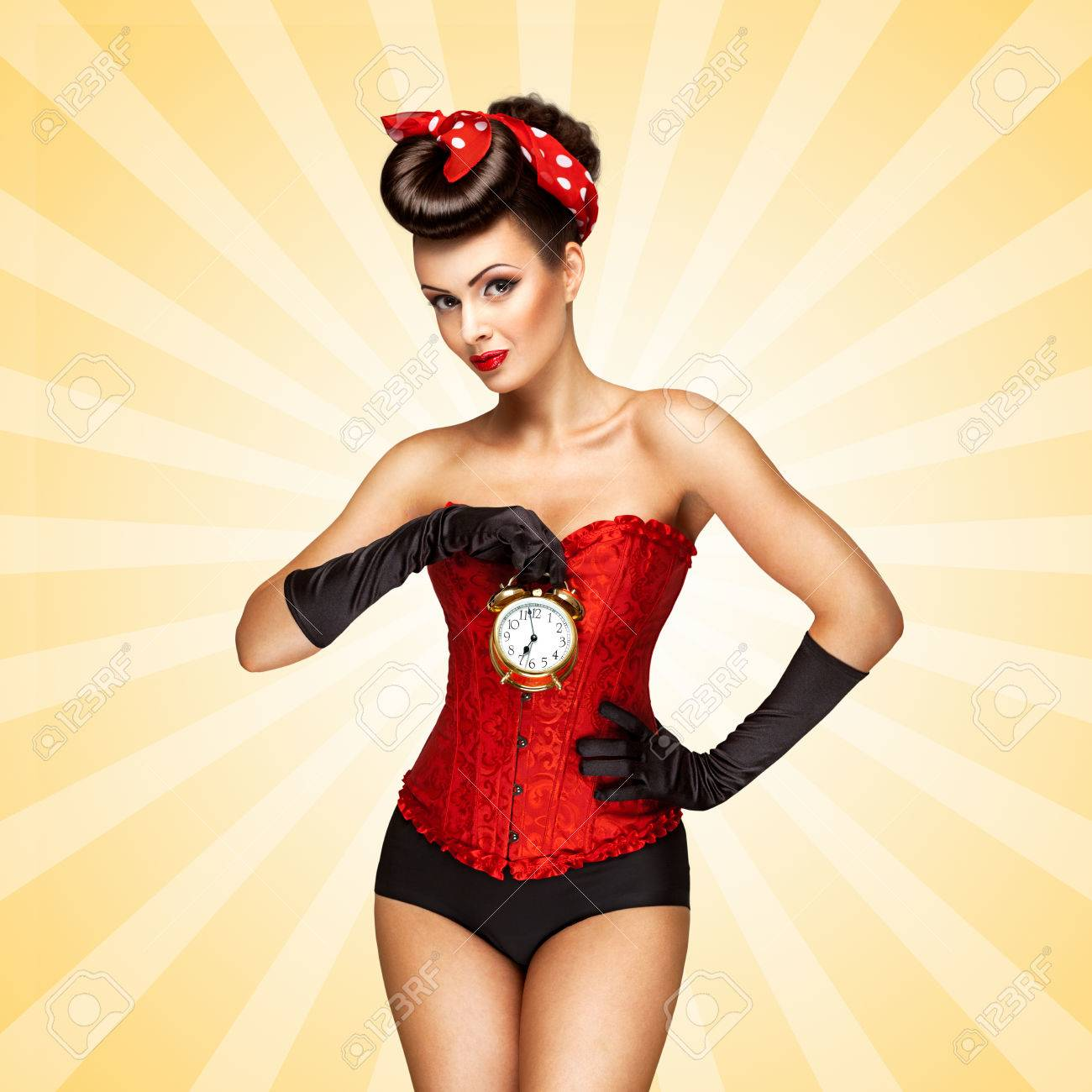 432c96cc8 Glamorous pinup girl in a red vintage corset holding a retro alarm clock in her  hand