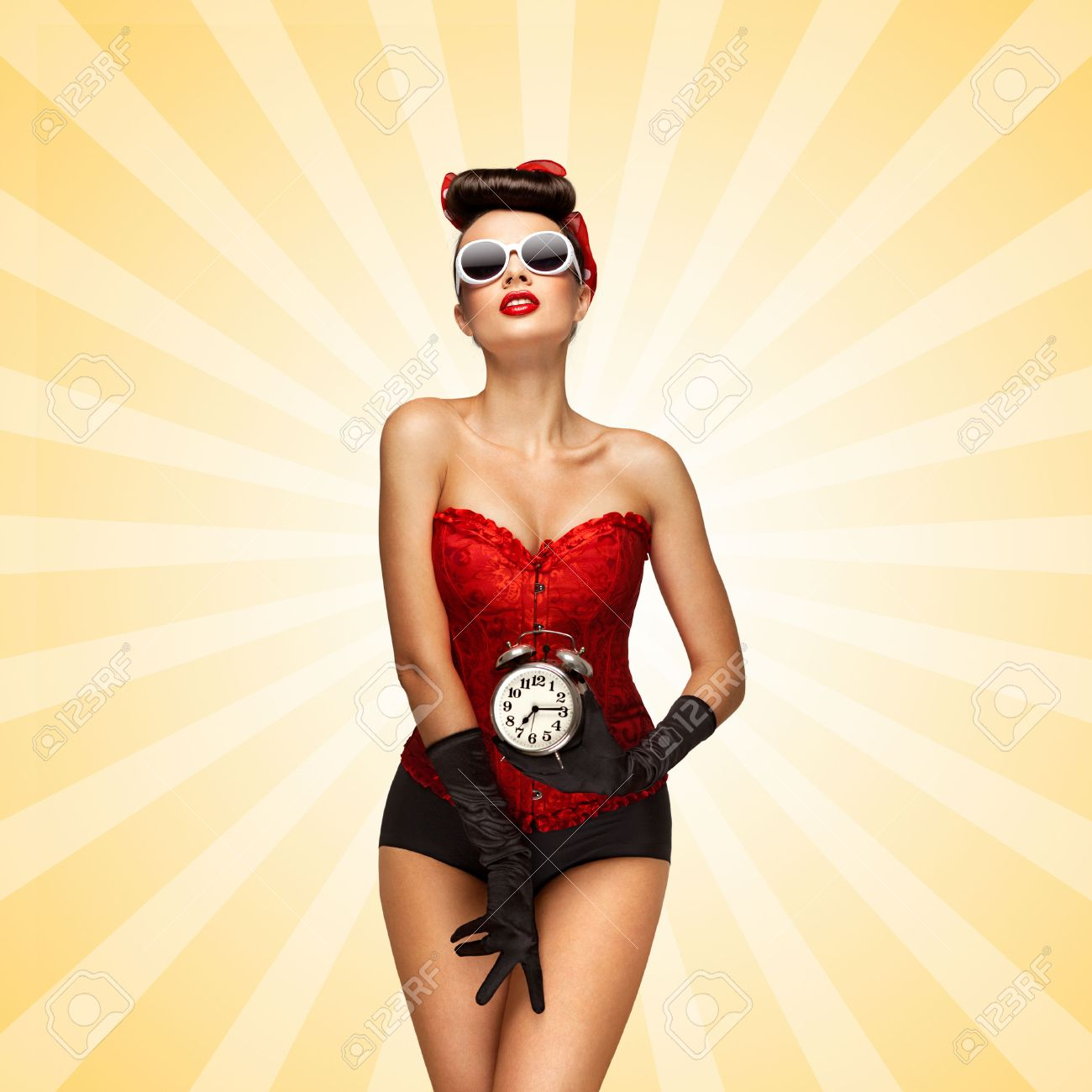 select for official good texture select for authentic Sexy pinup girl in a red vintage corset holding a retro alarm..