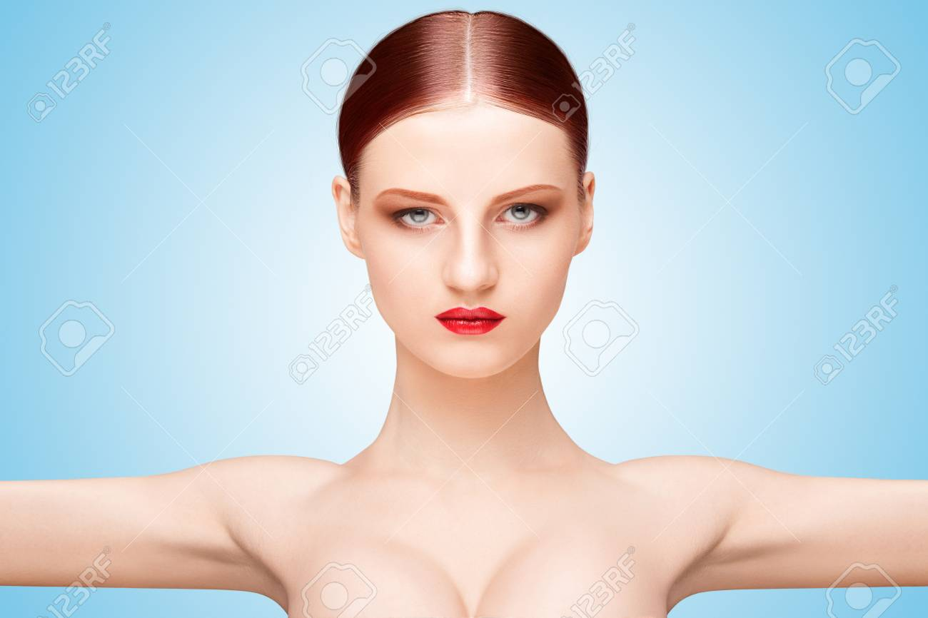 Front portrait of a nude girl with beautiful face and arms wide open on  blue background
