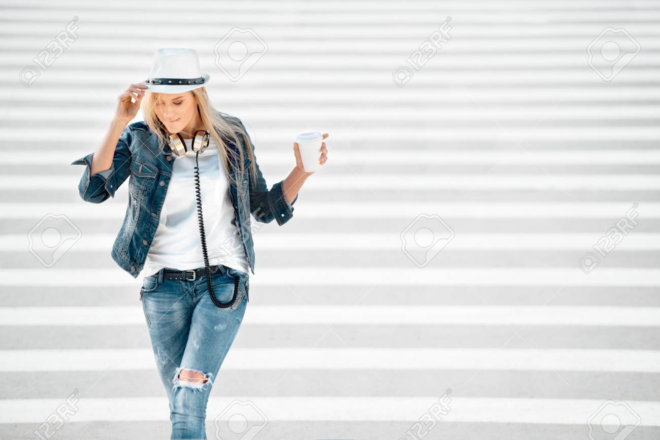 huge discount 5af93 1b52a Bella giovane donna in una giacca cappello e jeans con una tazza di caffè  da asporto, in piedi sulla strada con strisce pedonali, bere il caffè, e ...