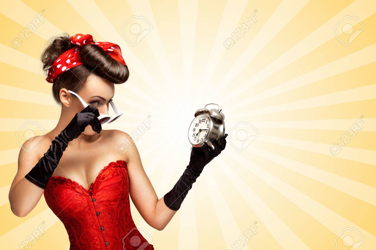 558aa1d9e Beautiful pinup girl in a red vintage corset being late in the morning and  holding a