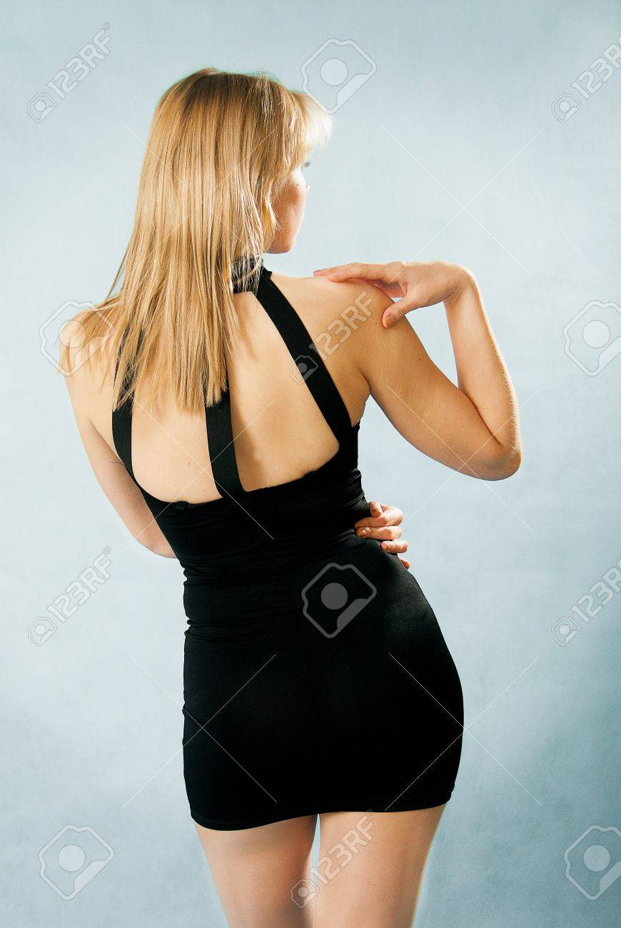 beautiful woman in sexy black dress standing with her back against blue background Stock Photo - 15761496