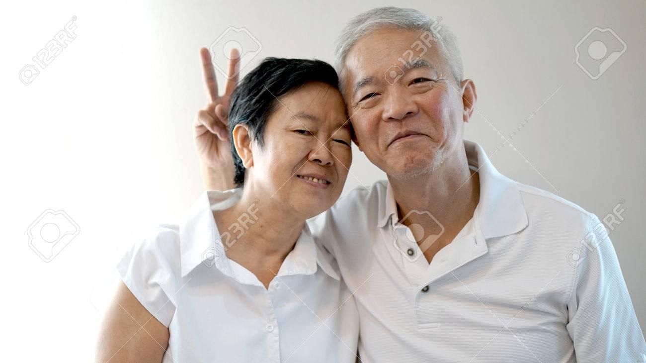 Happy Asian senior couple on white background love and hug - 43006508
