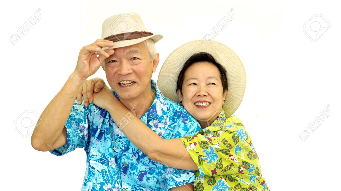 Happy Asian senior couple hugging happily wearing hat ready for holiday trip - 50614587