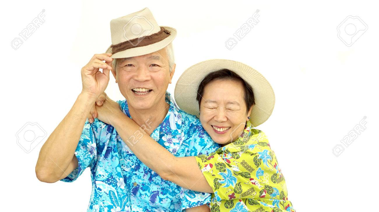 Happy Asian senior couple hugging wearing hat ready for holiday trip - 50614591