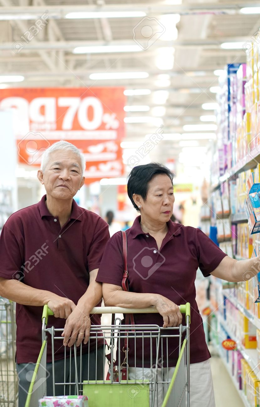 asian senior couple shopping at supermarket with cart - 60266909
