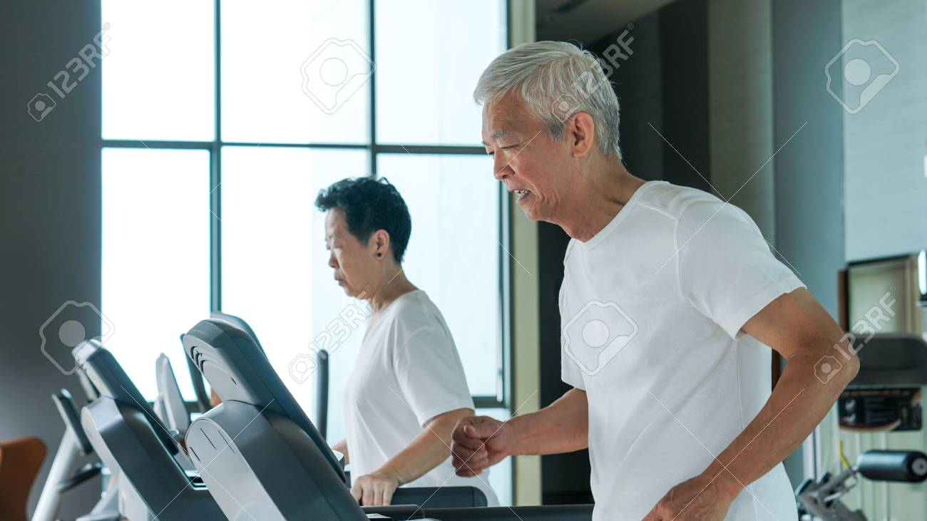 Old healthy Asian senior couple exercise together in gym running treadmill - 86375561
