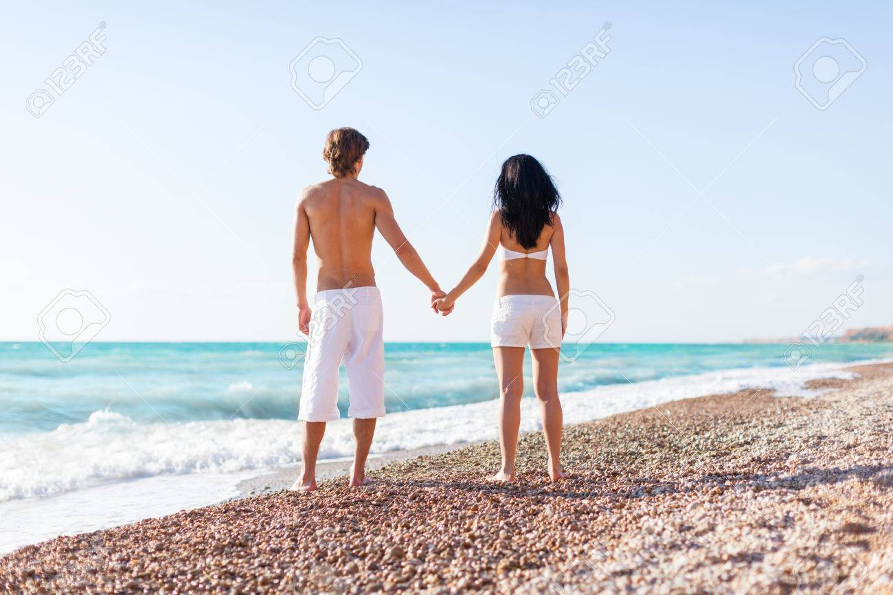 Couple De Dos couple on beach, rear view standing back love hold hands. full