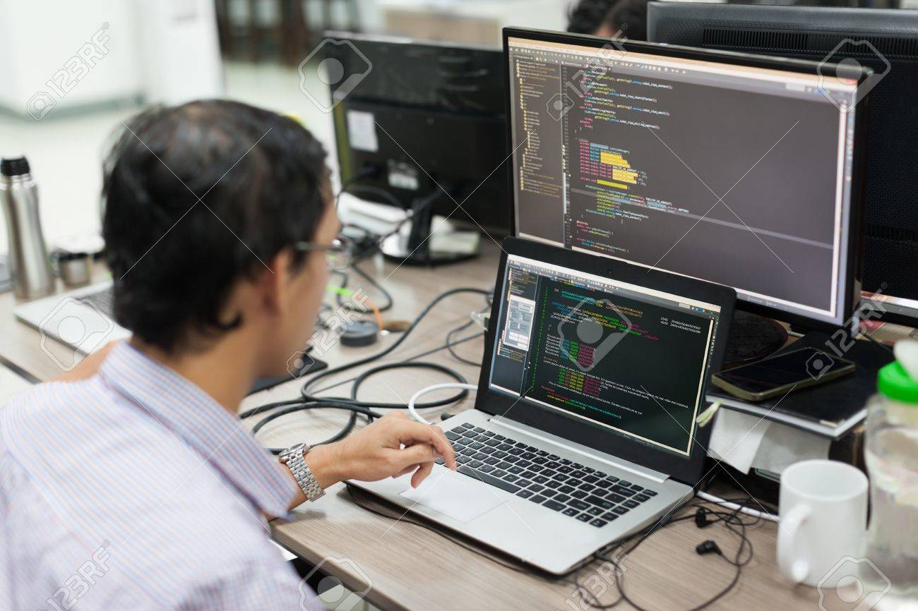 Asian outsource software developer regarder lécran assis à son