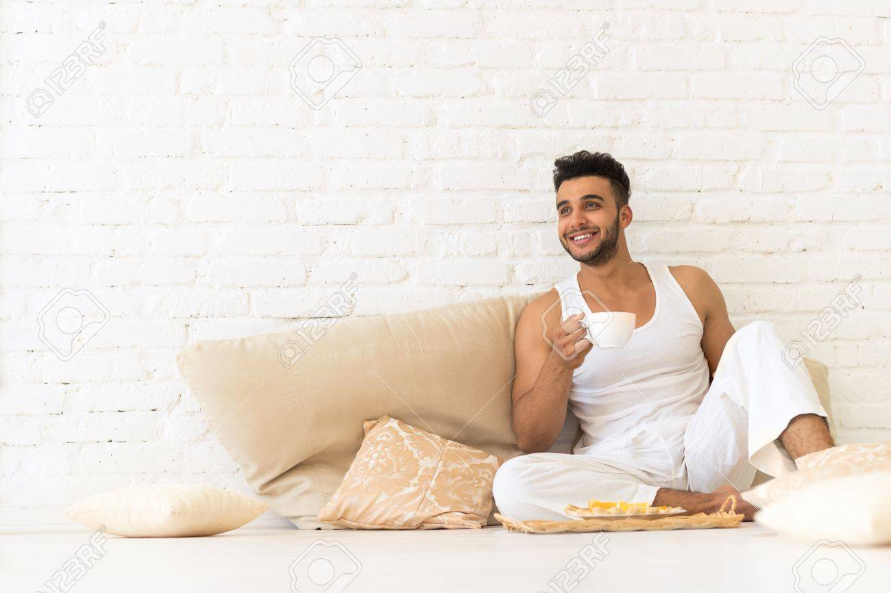Young Hispanic Man Sit On Pillows Floor, Happy Smiling Guy With ...