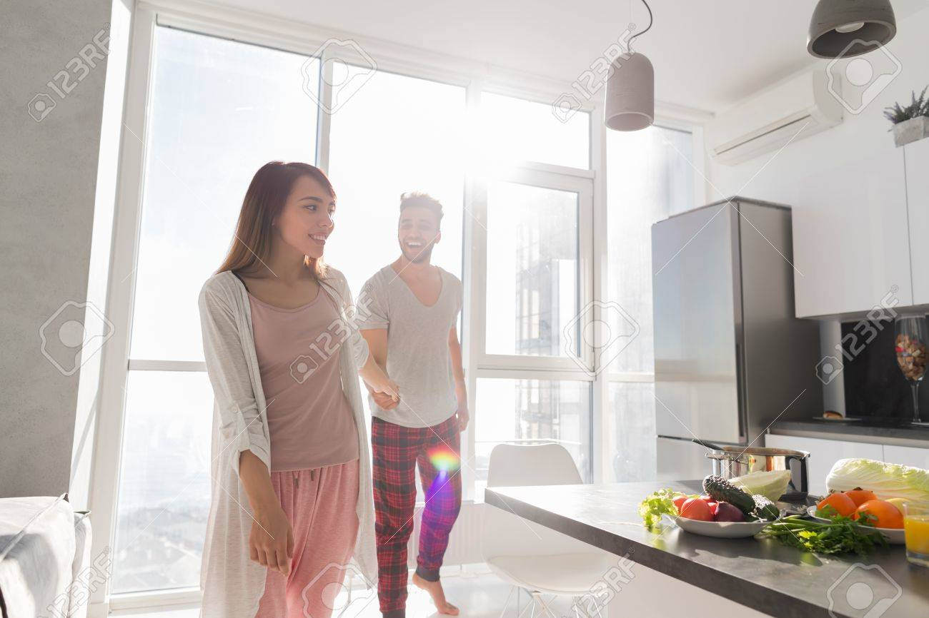 Young Couple Holding Hands In Kitchen, Asian Woman Leading Hispanic ...
