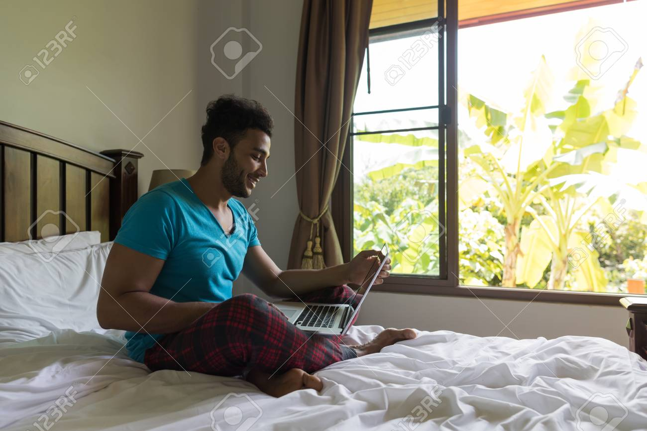 Stock Photo   Young Man Sit On Bed, Happy Smile Hispanic Guy Bedroom Using  Laptop Computer Hotel Room Interior